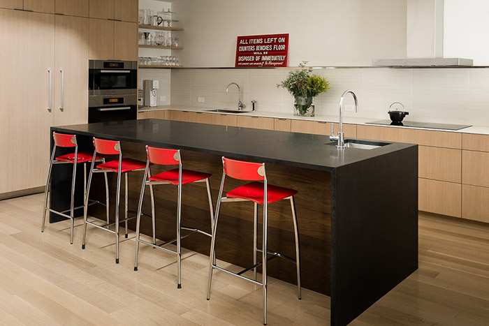 Contemporary kitchen design with modern red chairs