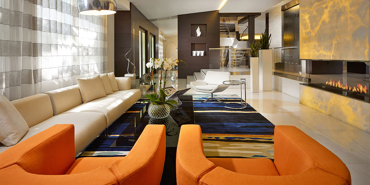 Luxurious Living Room With Modern White Sofa, Orange Armchairs And Beautiful Fireplace