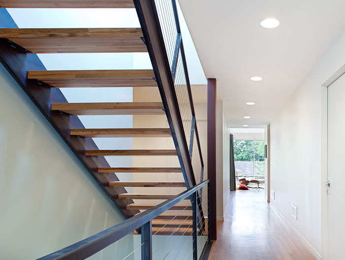 Steel Staircase Connecting The Top Levels Of The House To The Open-Plan Kitchen And Living Area