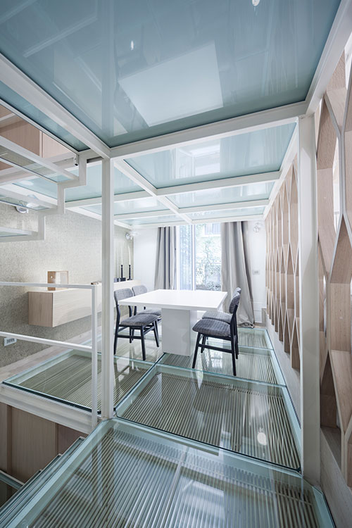 Gorgeous dining area design and glass floor in a beautiful three-level Italian apartment by Archiplan Studio