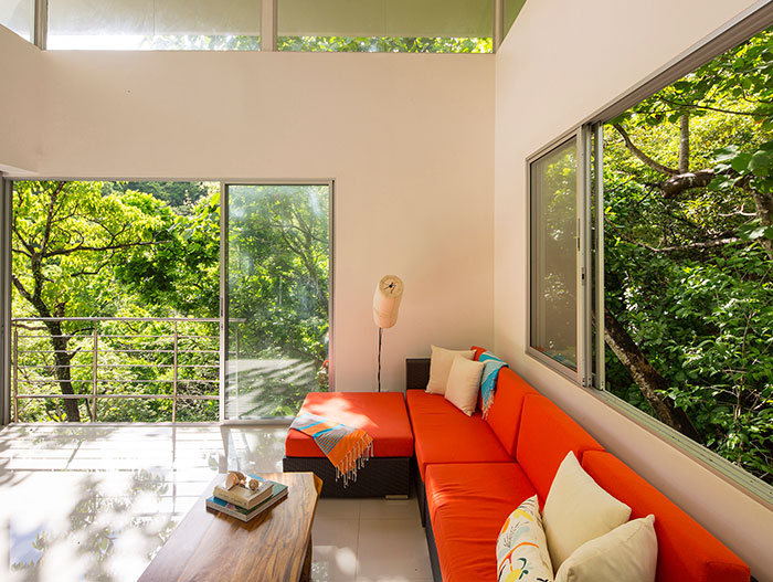 Seagull House by Indigo Arquitectura: Colorful living room design idea in amazing suspended house in Costa Rica that blends with the dense forest