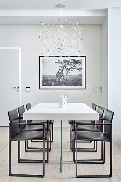 Beautiful dining table and contemporary lighting fixture in comfortable and sophisticated apartment by Alexandra Fedorova Architectural Bureau