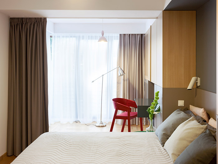 Modern bedroom design with small wood desk and red chair in a stylish, functional apartment in Bucharest by Rosu-Ciocodeica