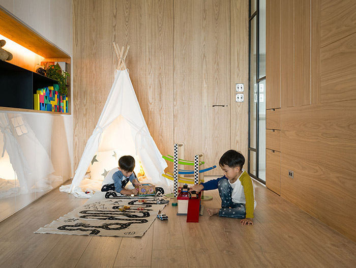 Play space with a teepee and plenty of toys  for kids in an inviting apartment by Awork Design Studio