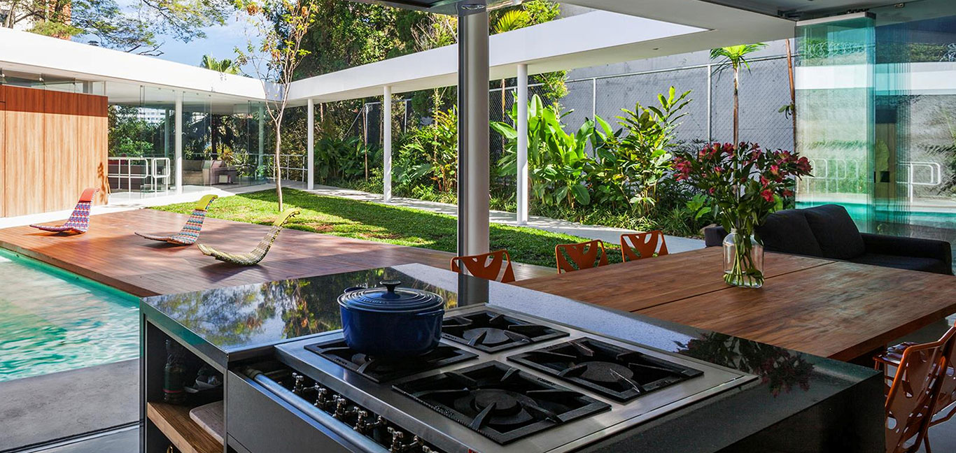Modern kitchen overlooking patio and swimming pool in incredible house in Sao Paulo Brazil by FGMF Architects