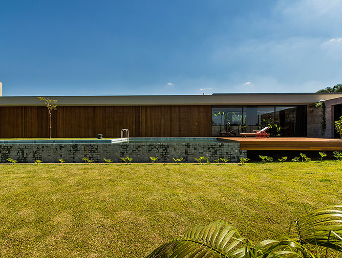 This wooden and concrete single-family house with stunning pool by mf+arquitetos, located near Sao Paulo, was inspired by Brazilian modernism
