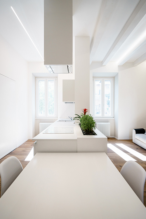 All-white minimalist apartment with open-space kitchen, dining and living area in Rome, Italy by Brain Factory - Architecture & Design
