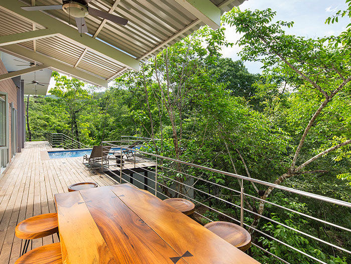 Relaxing terrace of a suspended Costa Rican house that blends with the dense forest - by Indigo Arquitectura