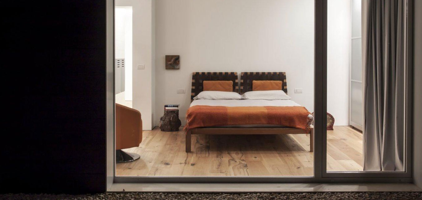 Minimalist bedroom in a sophisticated home in perfect balance with the surrounding environment - located in Italy, renovated by m12 AD