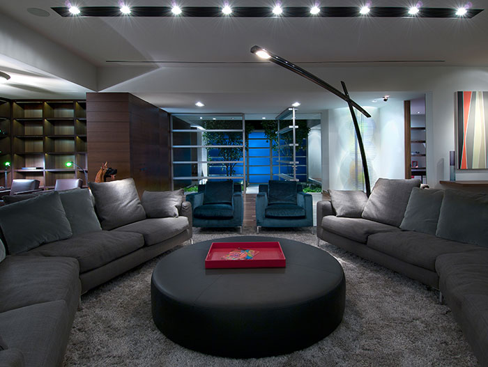 Contemporary living room design with oval coffee table in Californian home by Whipple Russell Architects