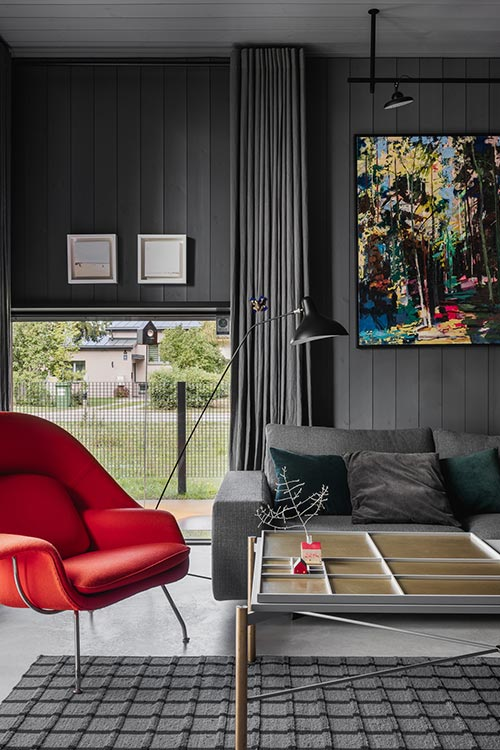 Modern timber house with dark interior and pops of color