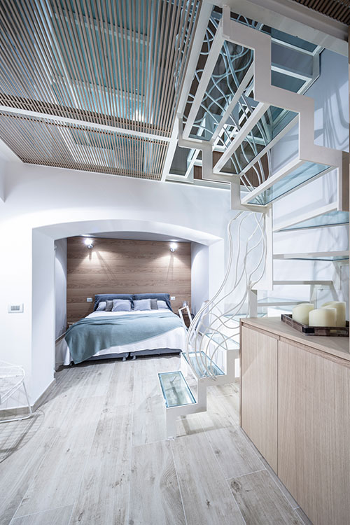 Stylish bedroom design and gorgeous glass staircase in a beautiful three-level Italian apartment by Archiplan Studio