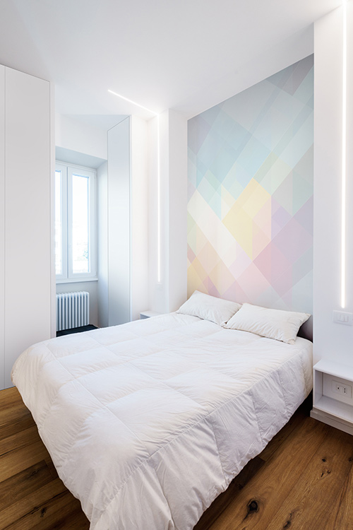 Beautiful white bedroom design idea with a colorful wall in a minimalist apartment in Rome, Italy by Brain Factory - Architecture & Design