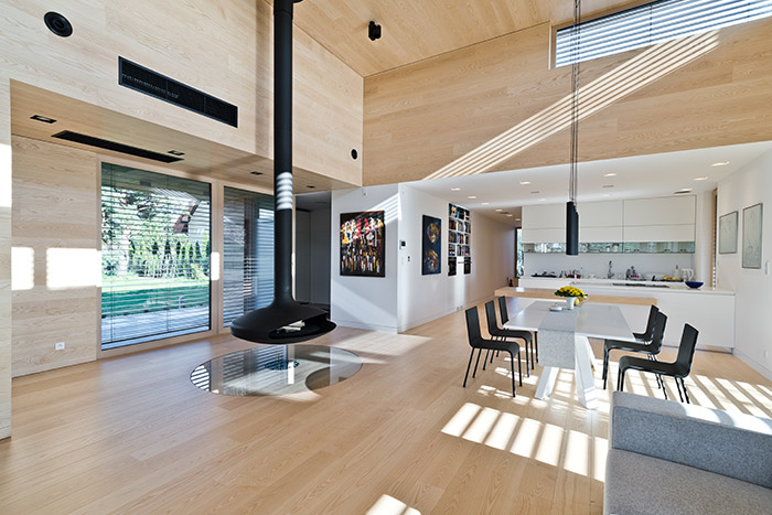 Single-storey house in Poland, clad almost entirely with cedar planks, has impressive double-height suspended fireplace in the open plan living room