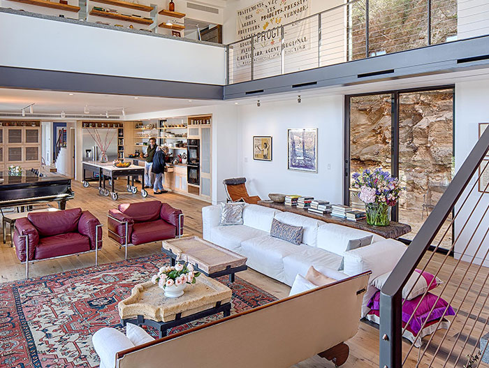 Eclectic interior design of living room in cliff dwelling by Specht Architects