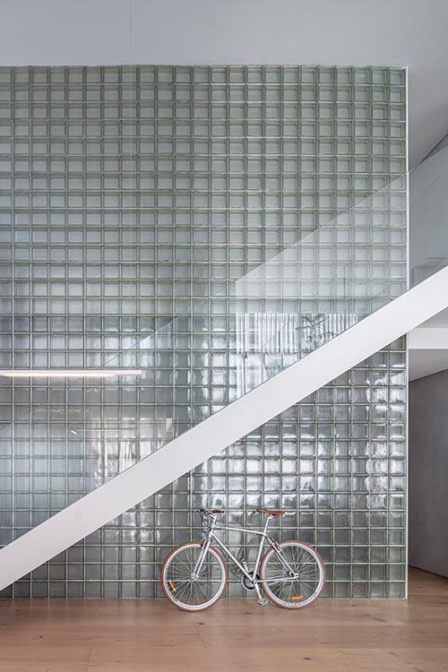 A glass block wall transfers light and creates reflections in a duplex apartment