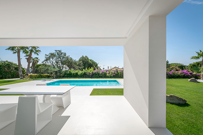 View of swimming pool and outdoor garden from dining area inside modern house outside Barcelona, Spain
