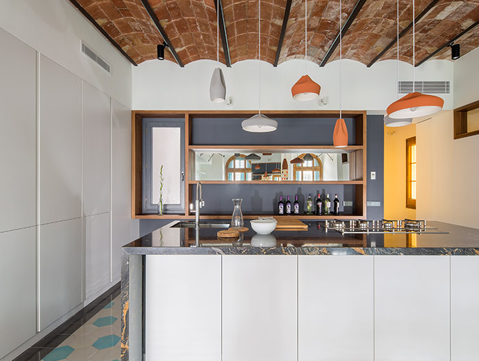 Gorgeous kitchen design idea in a stunning apartment in Barcelona that uses mirrors to amplify space and light