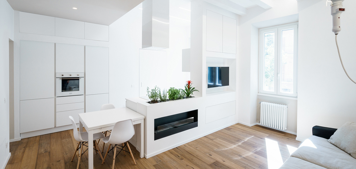 Modern kitchen design idea with multifunctional wall in an all-white minimalist apartment in Rome, Italy by Brain Factory - Architecture & Design