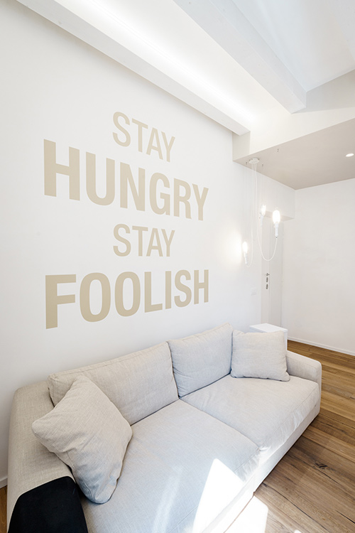 Beautiful living room design with inspirational wall writing in a minimalist apartment with all-white interior in Rome, Italy