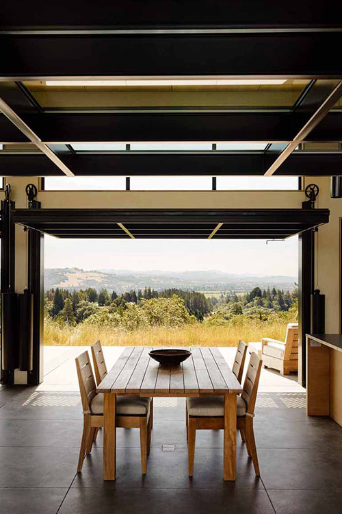 Amazing dining room opens to spectacular California wine country surroundings through massive glass walls - designed by Feldman Architecture