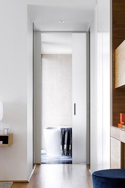 Beautiful modern hallway leading to bathroom inside contemporary Australian home