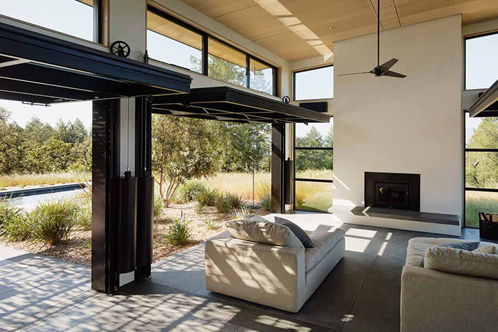 Modern living room design idea - massive glass walls connect interior to spectacular Californian wine country surroundings