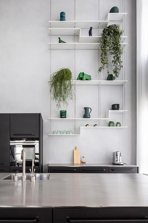 Black kitchen design with modern shelving in a bright duplex apartment