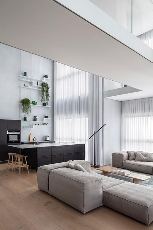 Modern open plan living room and kitchen in a bright duplex apartment