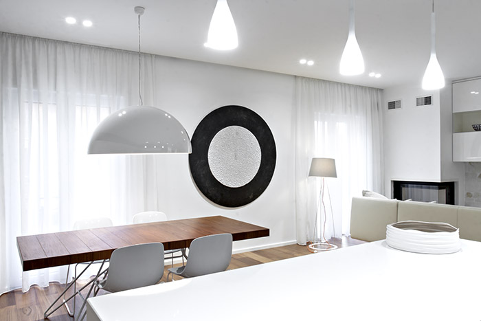This renovated apartment in Italy with open-space interior boasts elegant black and white palette and custom cabinets