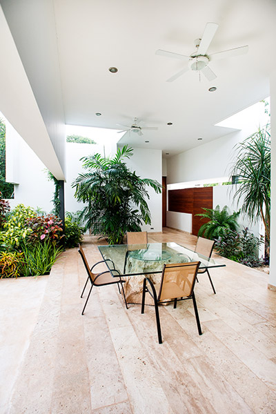 Amazing outdoor lounge area overlooks large living room, swing chair and lush garden - designed by Seijo Peon Architects