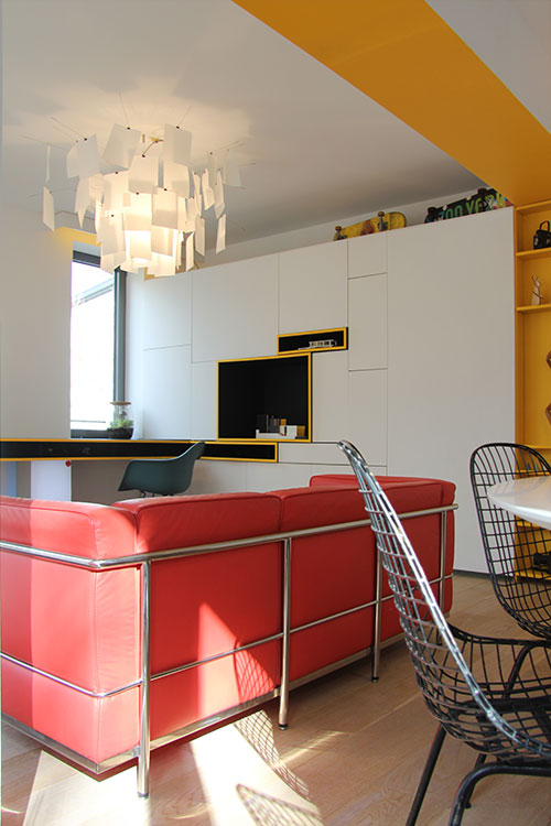 Red sofa and modern furniture add color to this apartment located in Belgium