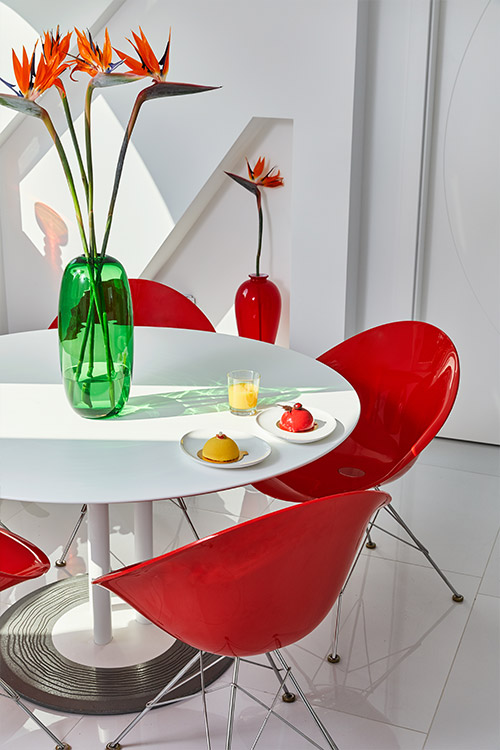Glossy red dining chairs add color in renovated apartment
