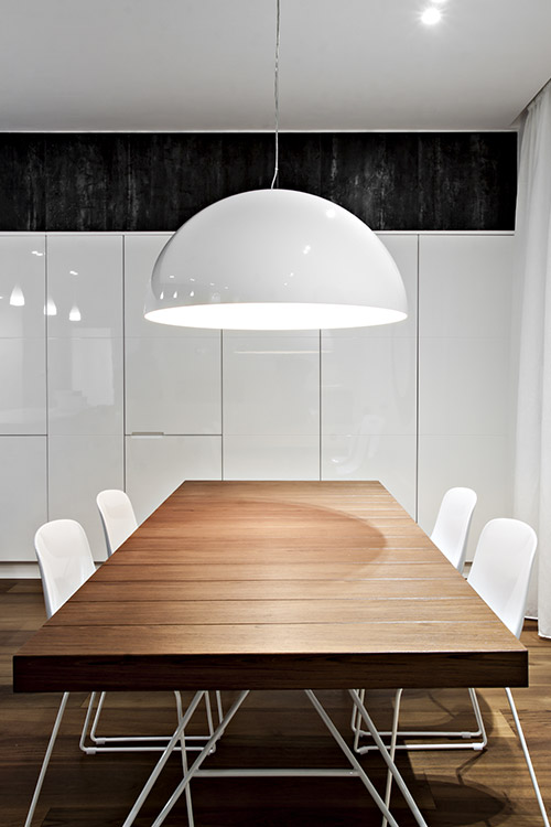 This modern dining room has a black and white palette and custom cabinets - the renovated apartment is located in Italy and was designed by  Michelangelo Olivieri / m12AD