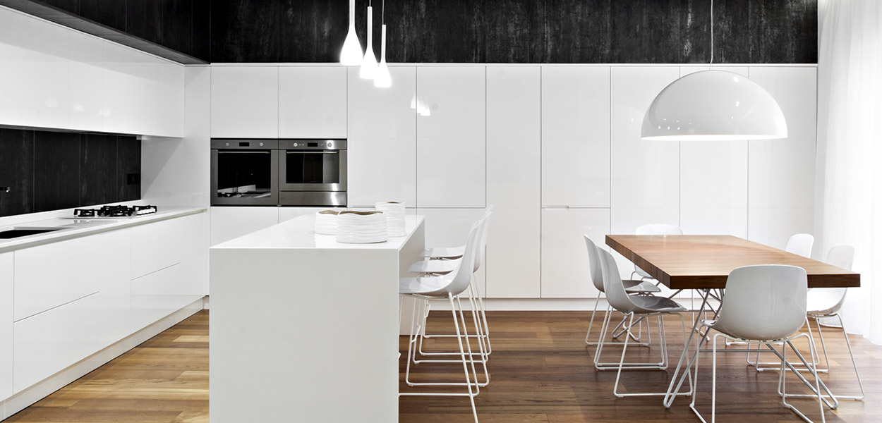 Renovated apartment in Italy by M12 Architettura Design: the kitchen has an elegant black and white palette and custom cabinets