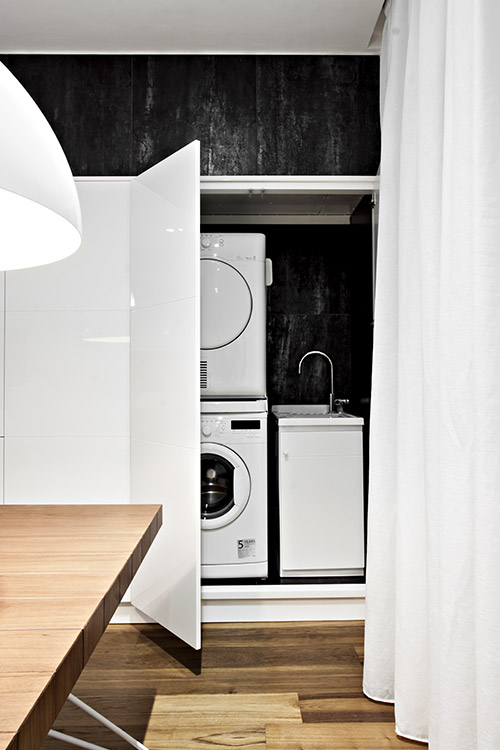 Modern kitchen with custom cabinets to hide the washing machine - renovated apartment in Italy