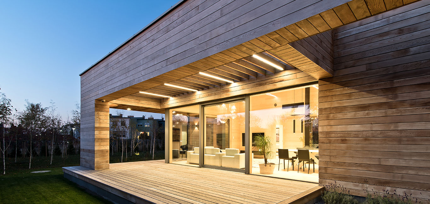 Single-storey house in Poznan, Poland is almost entirely clad in cedar planks and features big glazing for seamless indoor-outdoor transition