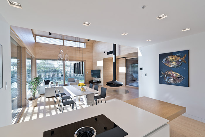View of living room from open space kitchen area - inside single-storey house in Poland entitled Cedar House