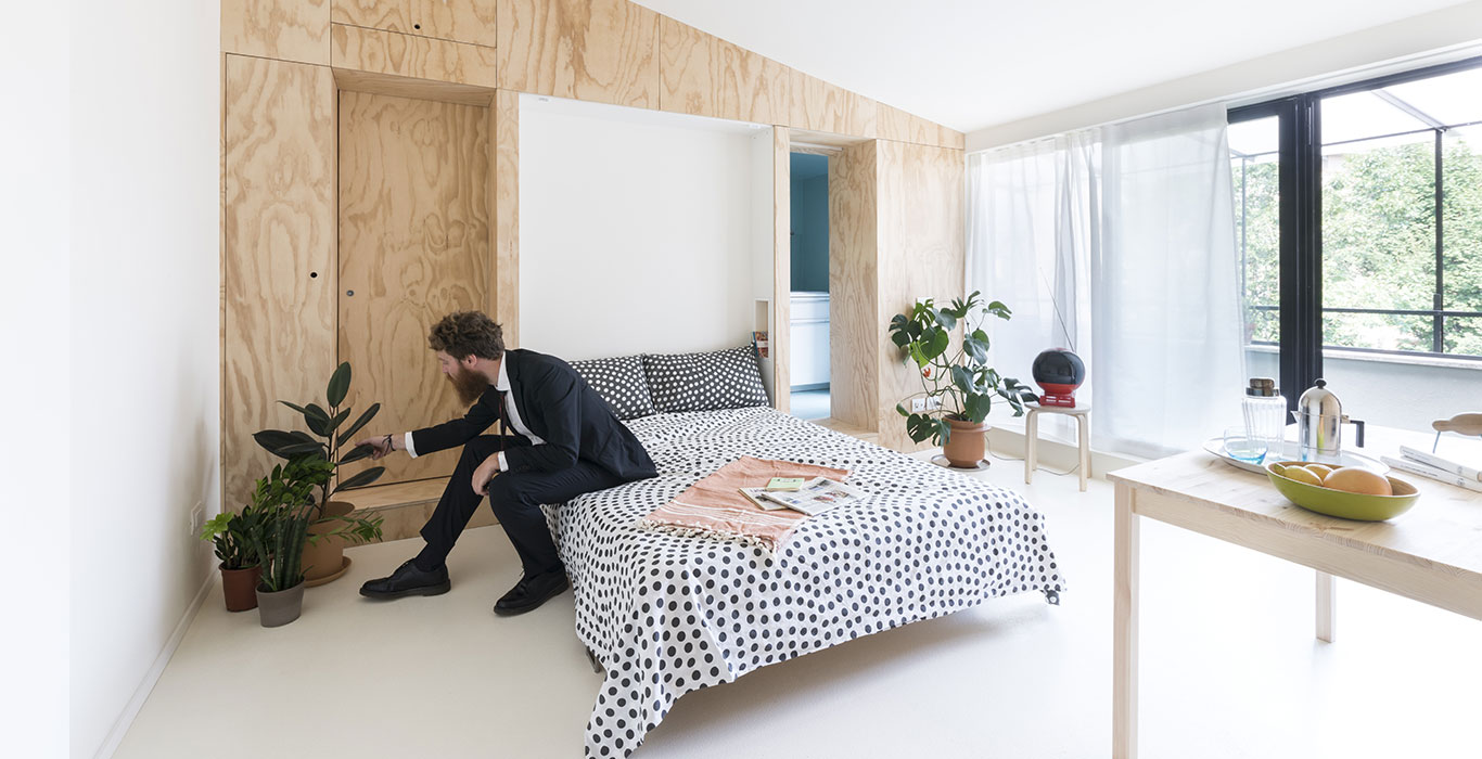 Small 28 square meter apartment in Milan gets modern remodeling which includes a multifunctional furniture piece that hides floating double bed