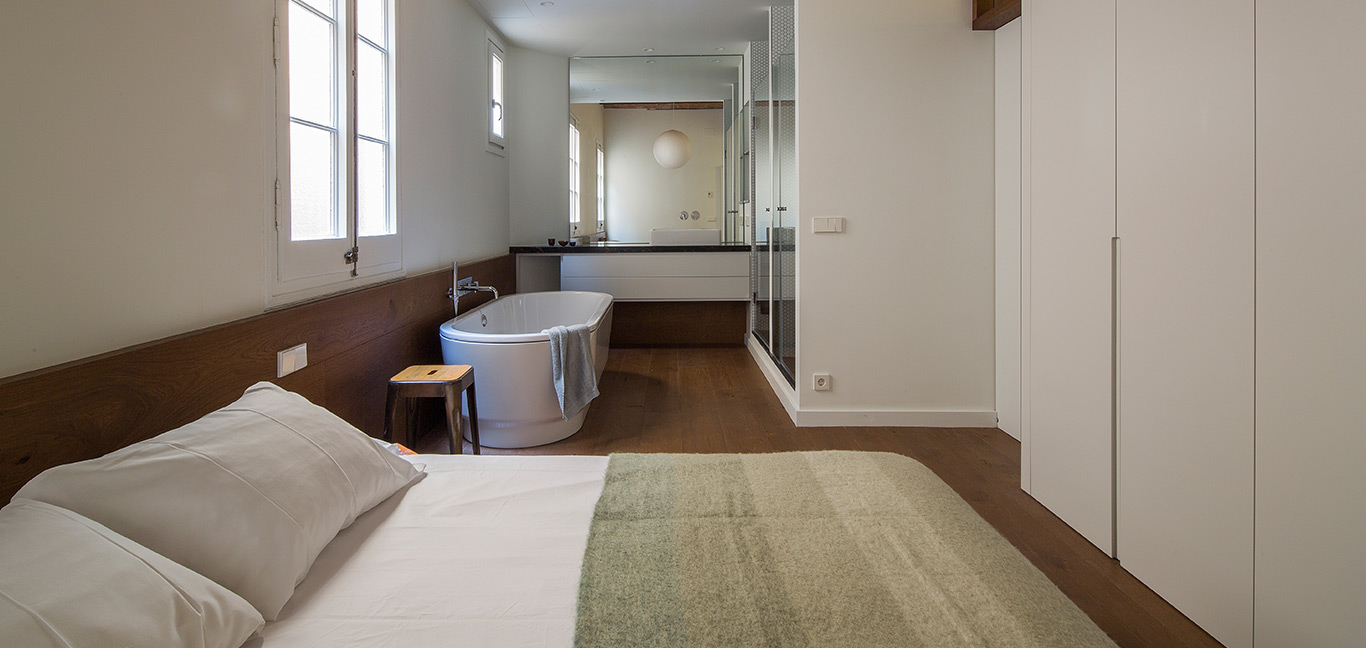 Bathtub in the corner of a modern bedroom - stunning apartment in Barcelona by Nook Architects