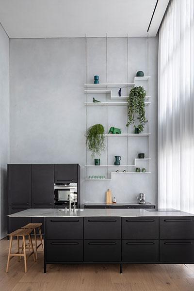 Modern black kitchen in a bright duplex apartment in Tel Aviv, Israel